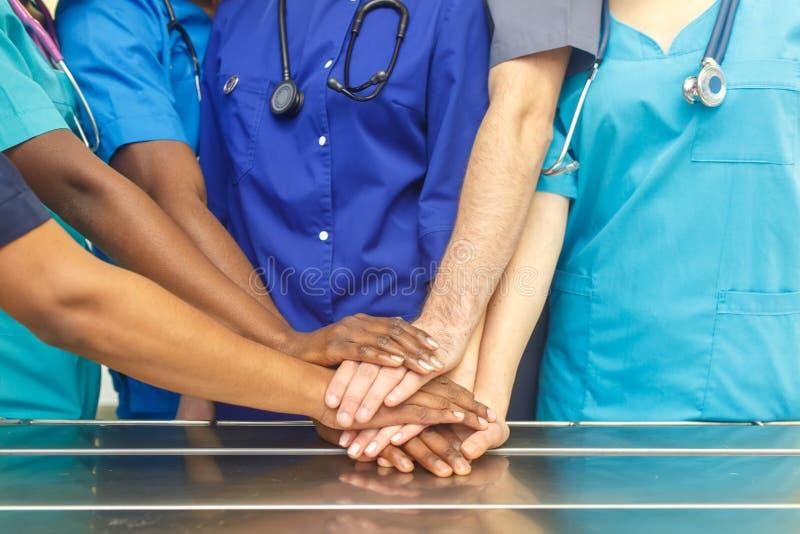 Gemischtrassiges Team von jungen Doktoren, welche die Hände Innen, Gruppe des gemischtrassigen Doktorchirurgieteams stapelt Hände stockbilder