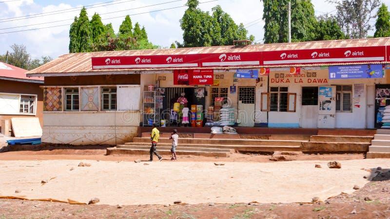 Gemischtwarenladen mit den Jungen, die vorbei in Front in ländlichem Tansania nahe Moshi gehen lizenzfreies stockfoto