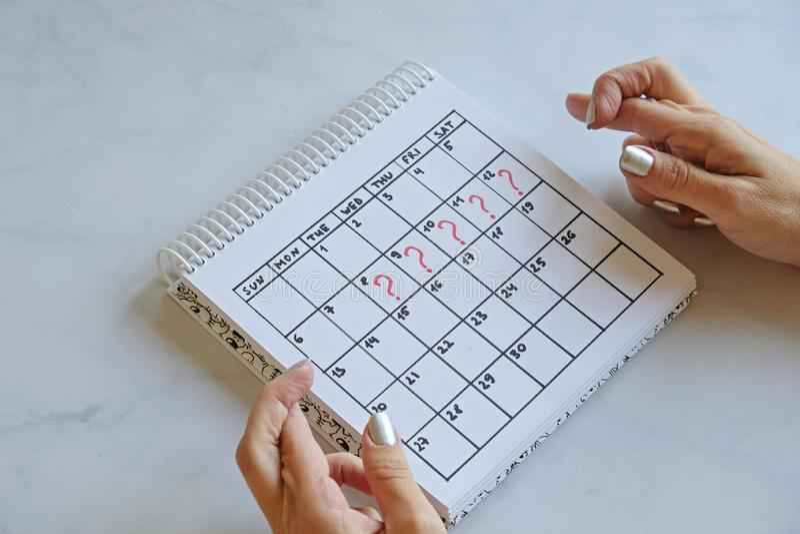 Gemiste periode gemarkeerd op kalender Vrouw met gekruiste vingers Ongewenste zwangerschap en vertraging in de menstruatie stock afbeeldingen
