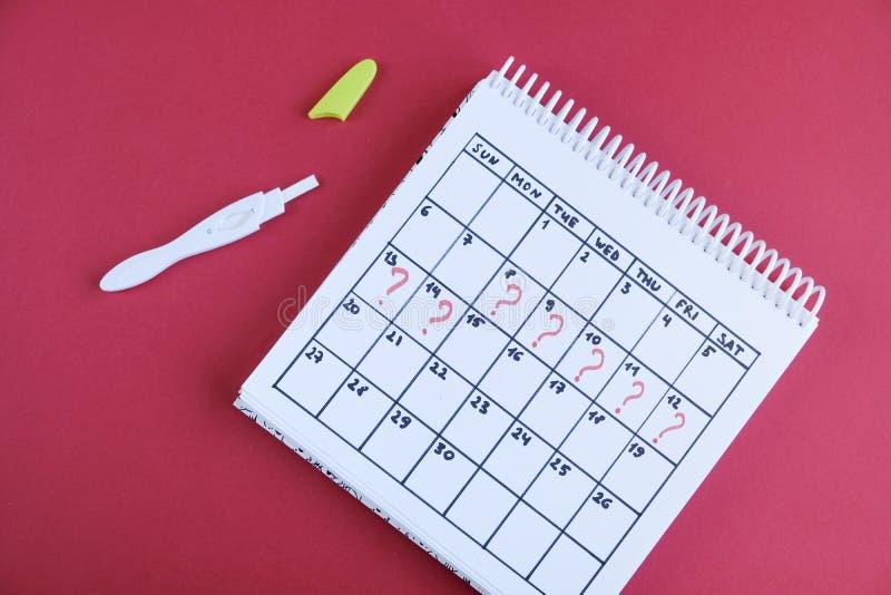 Gemiste periode gemarkeerd op kalender, zwangerschapstest De gezondheid van de vrouw en vertraging in menstruatie stock afbeeldingen