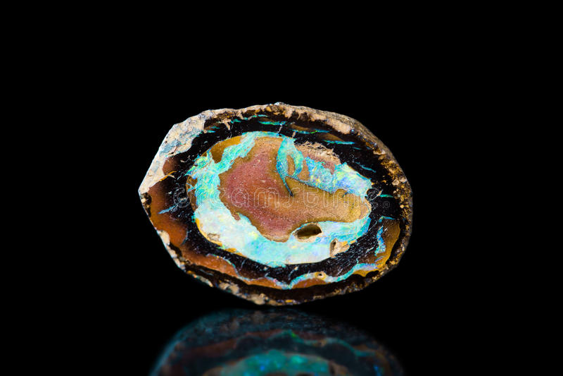 Gemme d'opale de feu, pierre curative, fond noir, minéral image stock