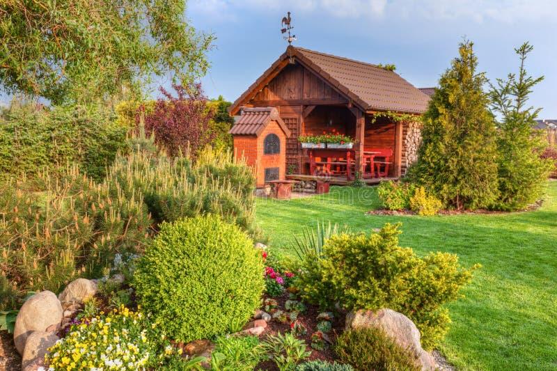 Gemodelleerde de zomertuin met barbecue en houten summerhouse Groene bomen, bloembedden, stock foto