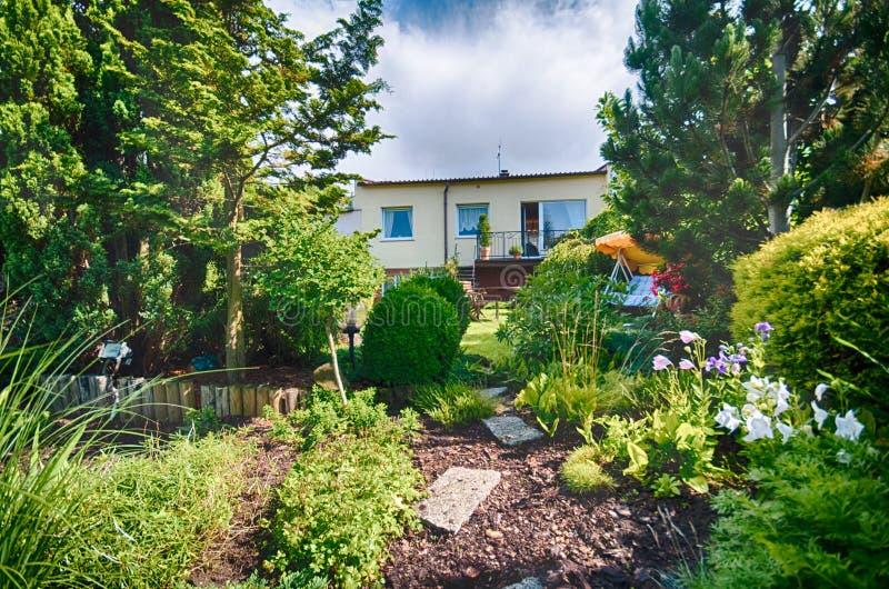 Gemodelleerde tuin in de zomer in weelderige groene kleuren royalty-vrije stock foto