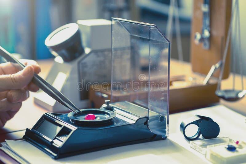 Gemologist que califica la piedra de gema del color rojo en laboratorio del gemology imagenes de archivo