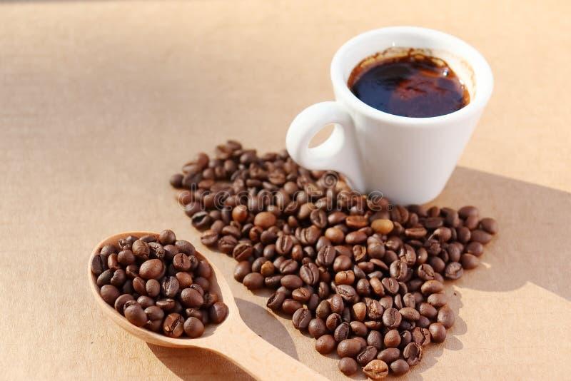 Gemorste koffie De korrels van aromatische geroosterde koffie verspreidden zich in de vorm van een hart op een kartonoppervlakte  stock afbeelding