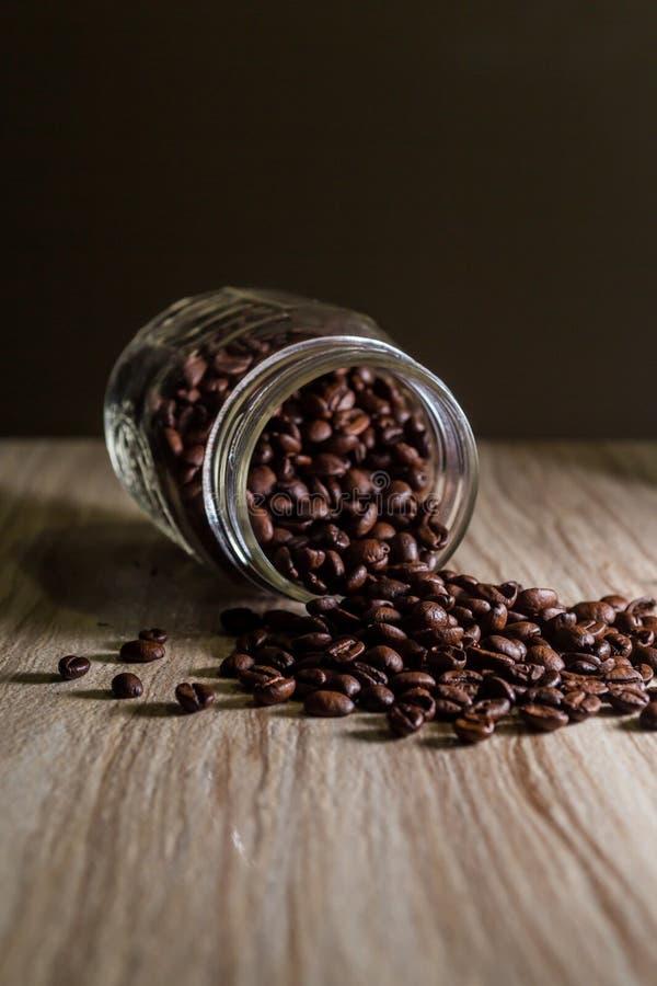 Gemorste koffiebonen van metselaarkruik op houten korreltextuur royalty-vrije stock foto