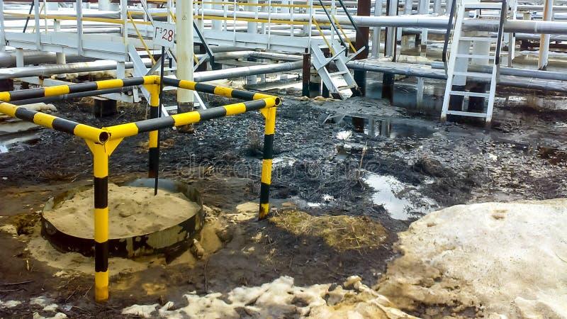 Gemorste olie op zandige grond dichtbij pijpleidingen en procesmateriaal Olielekken tijdens verrichting stock foto