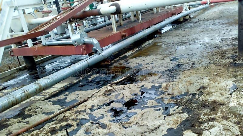 Gemorste olie op zandige grond dichtbij pijpleidingen en procesmateriaal Olielekken tijdens verrichting en royalty-vrije stock foto