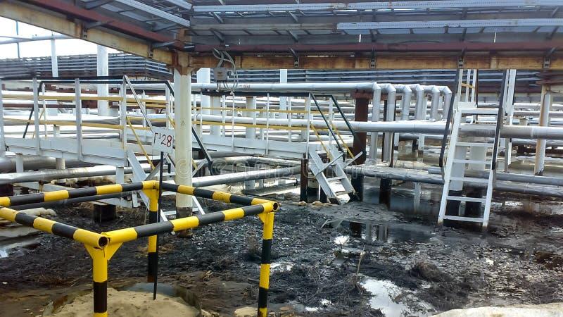 Gemorste olie op zandige grond dichtbij pijpleidingen en procesmateriaal Olielekken tijdens verrichting en stock foto