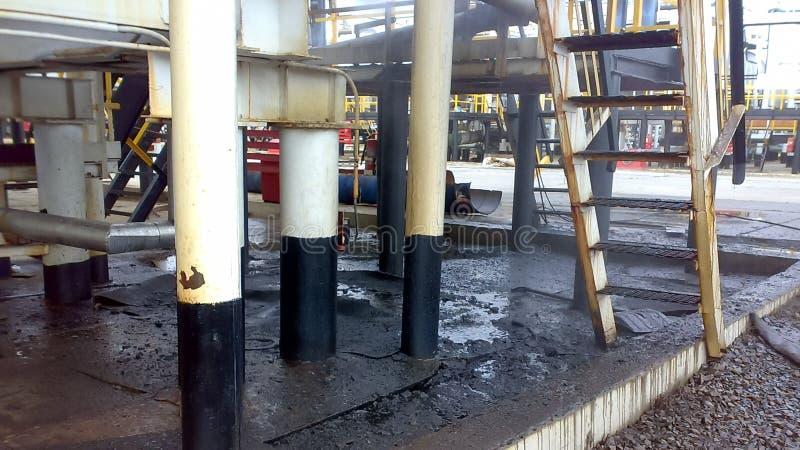 Gemorste olie op zandige grond dichtbij pijpleidingen en processnt Olielekken tijdens verrichting en reparatie stock afbeeldingen