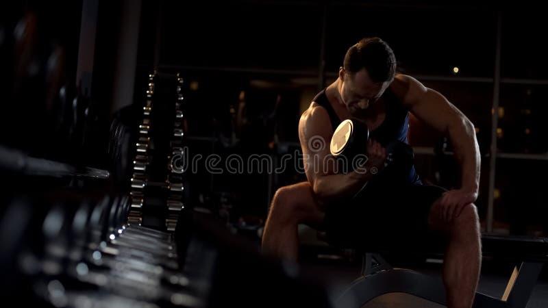 Gemotiveerde bodybuilder die gezette domoorkrul doen, die training gelijk maken stock fotografie