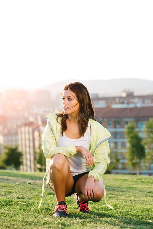 Gemotiveerde vrouwelijke atleet die in stadspark uitoefenen stock afbeelding