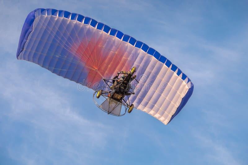 Gemotoriseerd glijscherm die in blauwe hemel vliegen stock afbeeldingen