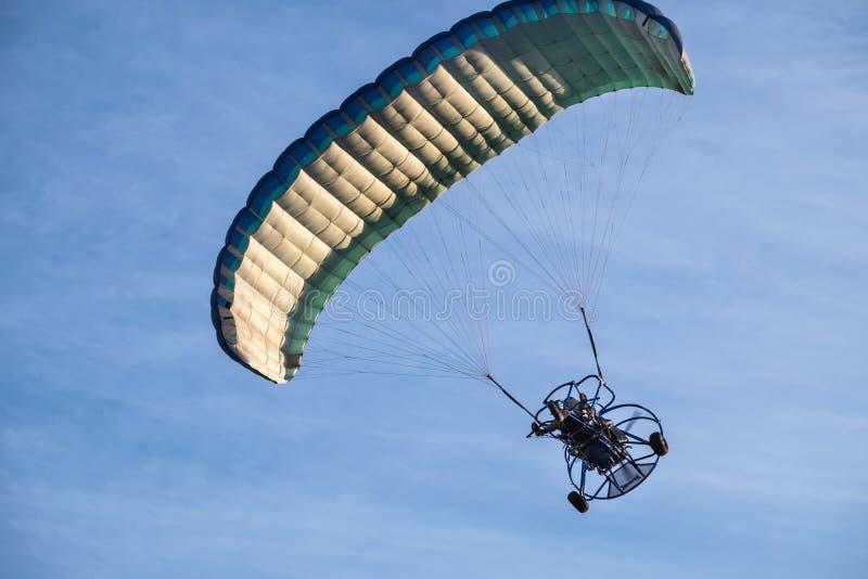 Gemotoriseerd glijscherm die in blauwe hemel in zonsondergangtijd vliegen stock afbeeldingen