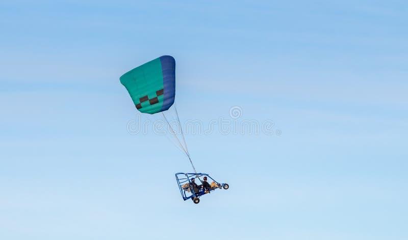 Gemotoriseerd glijscherm die in blauwe hemel in zonsondergangtijd vliegen stock fotografie