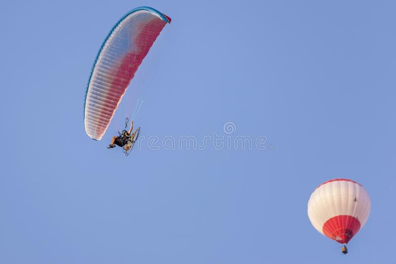 Gemotoriseerd glijscherm en hete luchtballon in een mooie blauwe hemel royalty-vrije stock foto