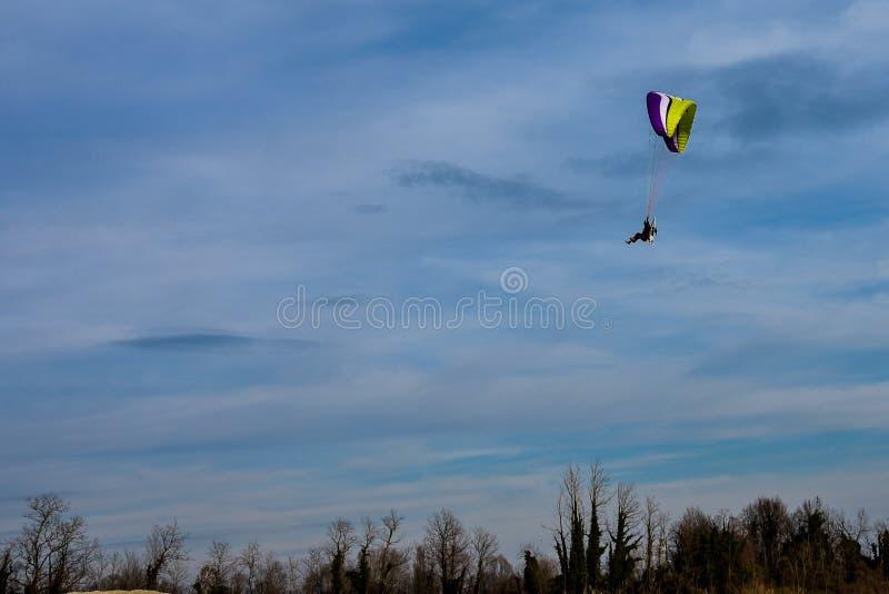 Gemotoriseerde deltavlieger die in de blauwe hemel stijgen stock afbeelding