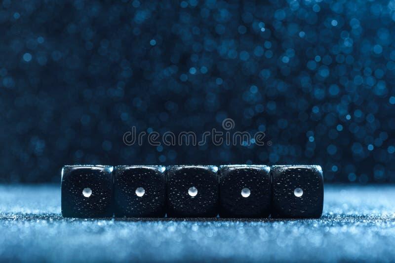 Gemowi sześciany są obok siebie Pięć identycznych czarnych sześcianów na błękitnym tle obrazy stock