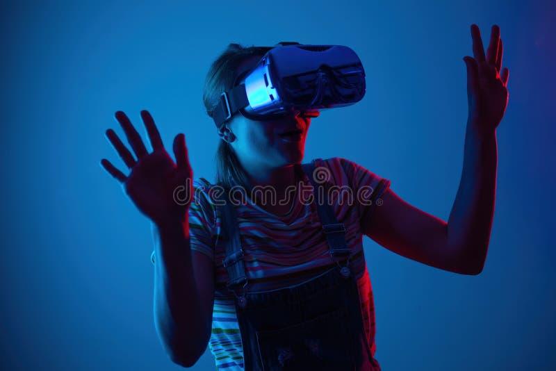 Gemowy vr Dziewczyna w hełmie z kontrolerem i bawić się grę z kreatywnie światłem obraz royalty free