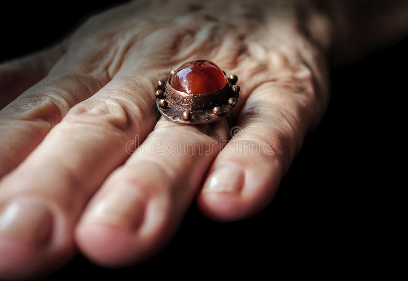 Gemstone Amber color ring with copper on older lady hand. This artistic ring is handmade by one artist in Serbia Southeast of Europe stock images