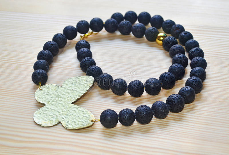 Gemstone black lava necklace with gold butterfly. Greek jewelry royalty free stock image