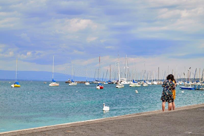 Genève, Zwitserland - 21 september 2018: Toerisme op de dijk in de buurt van een beroemde fontein op het meer in Genève op een m royalty-vrije stock afbeelding