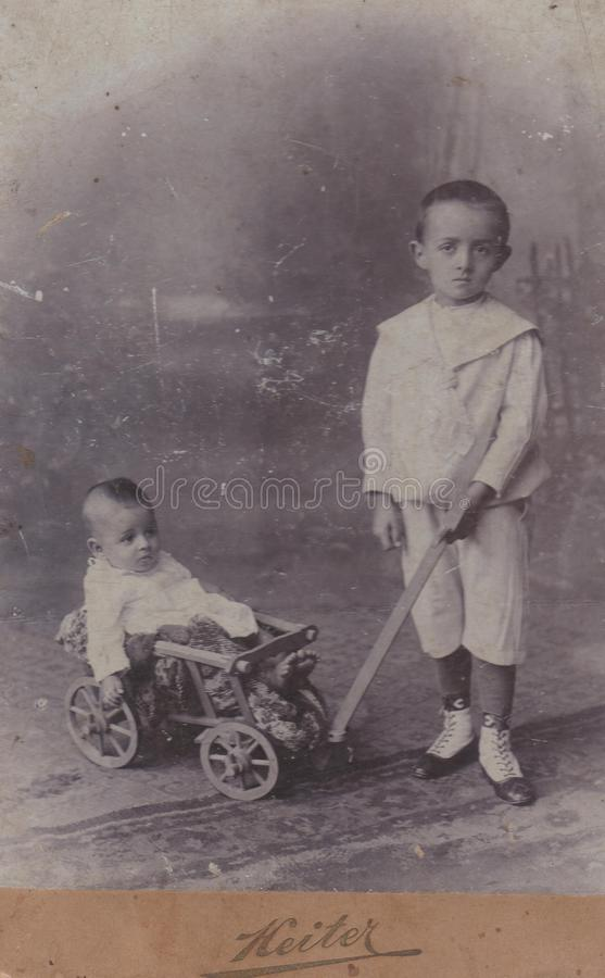 GEN REGHIN do ‰ do  SZRà de HUNGRIA SZà CERCA de 1890 - rapaz pequeno que tracting seu irmão mais novo com transporte - fotos do imagem de stock royalty free