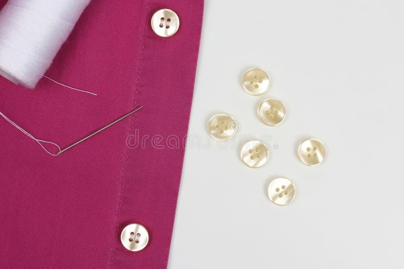 Genaaid met een naald met de witte knopen van de dradenparel op het overhemd stock foto