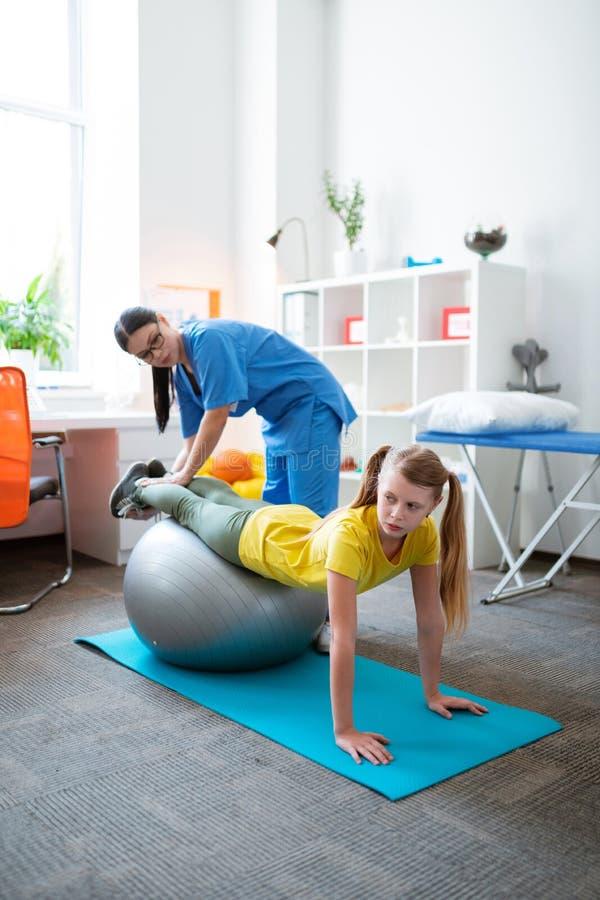 Genaues fleißiges Mädchen, das auf grauem Pilates-Ball sich lehnt stockfotografie