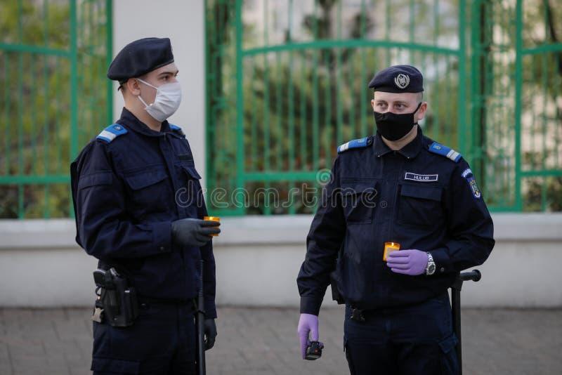 Gendarmes romenos com máscaras cirúrgicas devido à pandemia de 19 de setembro tomam a Luz Sagrada durante a Páscoa ortodoxa imagem de stock royalty free