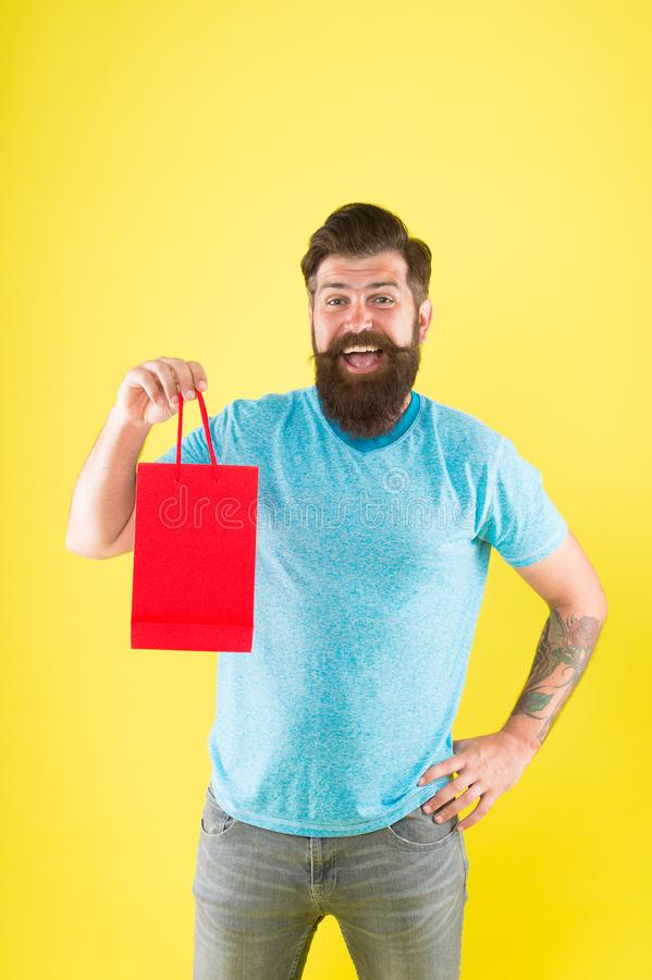 Gender differences in purchase decision making. Happy hipster hold paper bag. Bearded man smiling with fashion purchase royalty free stock photos