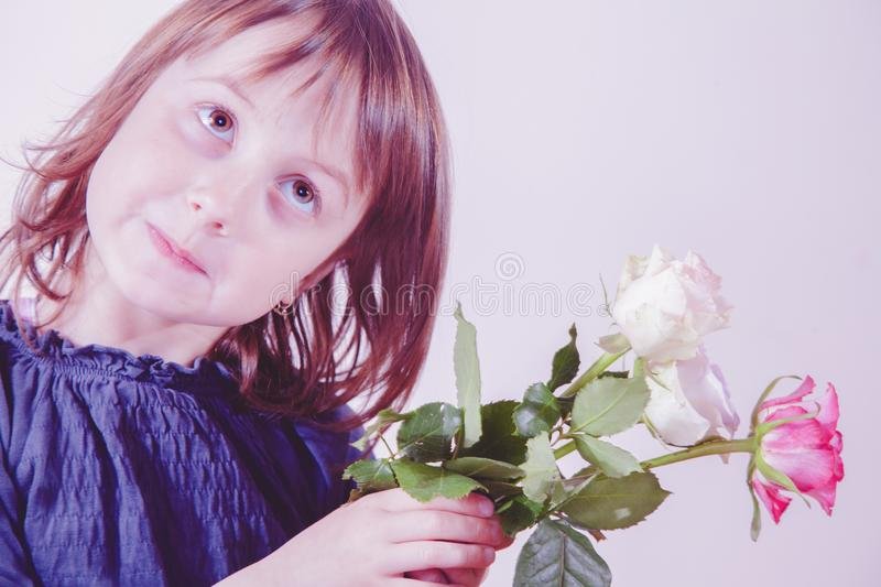 Gender identity development in early childhood concept. Beautiful little child girl with roses flowers. Selective focus on eyes stock photo