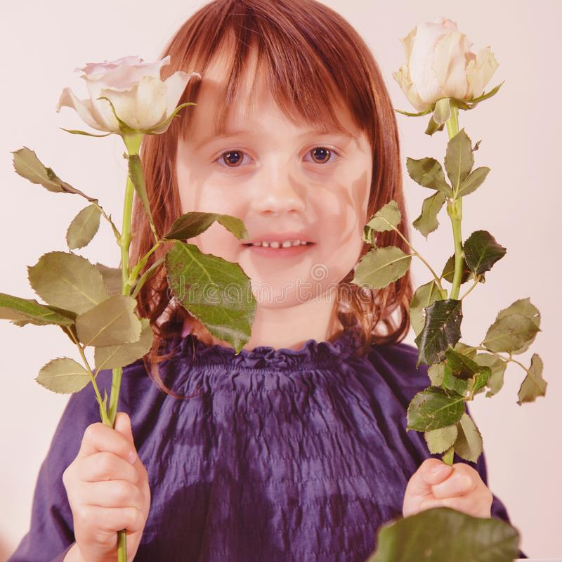Gender identity development in early childhood concept. Cute little child girl with roses flowers royalty free stock photography