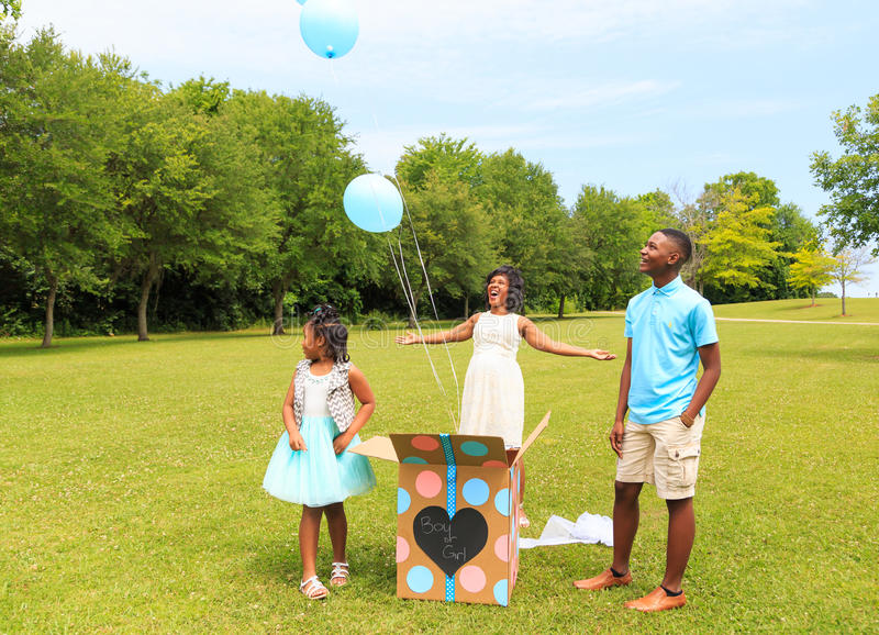 Gender Reveal Baloon Release. Beautiful African American Mother gives a room lighting smile as she reveals the gender of her child blue for boy to her daughter