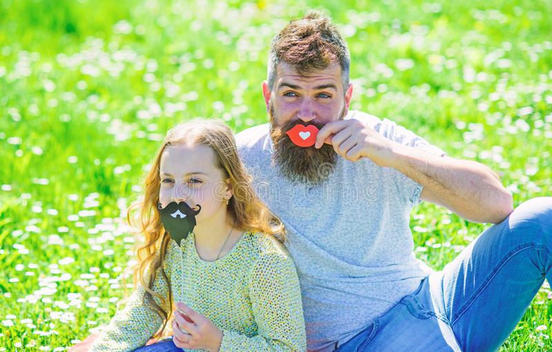 Gender roles concept. Family spend leisure outdoors. Dad and daughter sits on grassplot, grass on background. Father. Posing with lips and child posing with stock images
