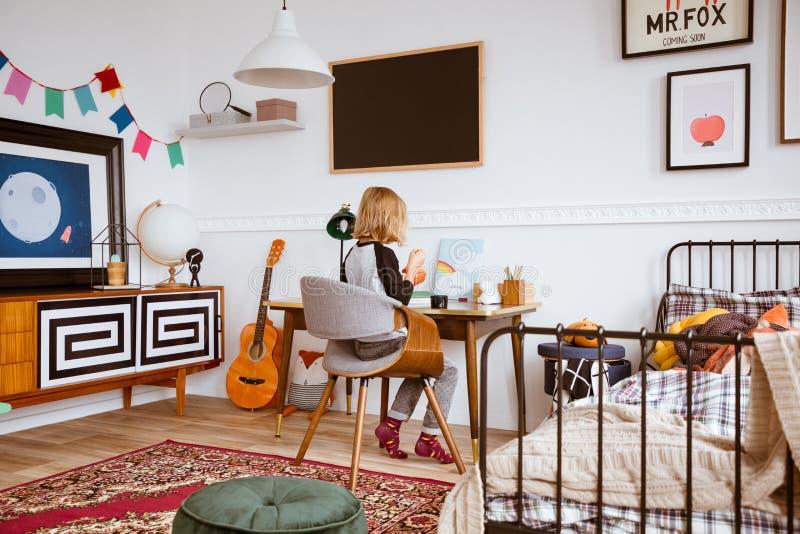 Genderless Schlafzimmer mit Kindermalerei am Retro- Schreibtisch im Wohnungshaus stockfoto