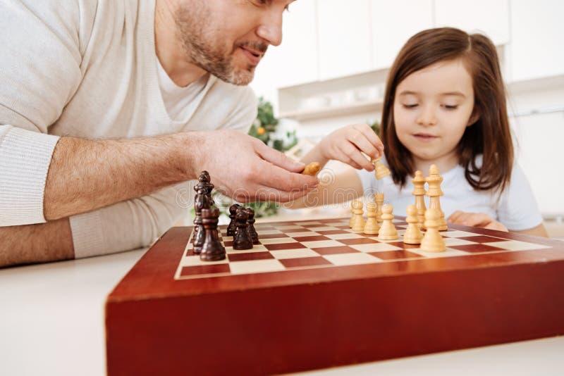 Gene a ajuda de sua filha estabelecer um tabuleiro de xadrez imagens de stock royalty free