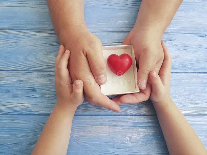 Gene as mãos paizinho do dia do ` s e o coração da caixa de presente da criança em um fundo de madeira azul fotos de stock