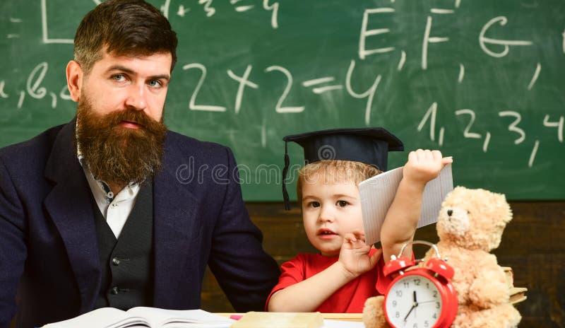 Gene com barba, professor ensina o filho, menino da criança Conceito de ensino da criança Professor e aluno no barrete, quadro so fotos de stock
