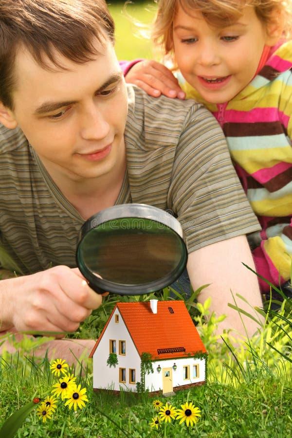 Gene com a menina que olha na casa através da lupa foto de stock royalty free