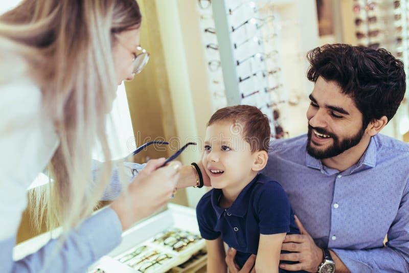 Gene com o filho que escolhe vidros na loja do sistema ótico fotografia de stock royalty free