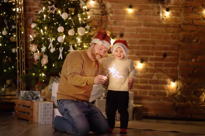Gene com seu Natal pequeno da celebração do filho com chuveirinho foto de stock royalty free