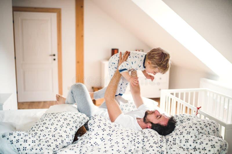 Gene com um menino da criança que tem o divertimento no quarto em casa em horas de dormir fotografia de stock