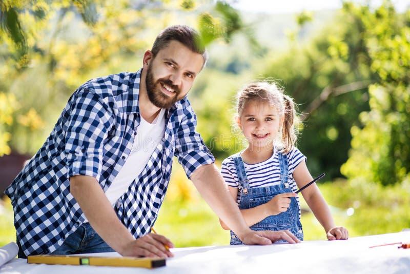 Gene com uma filha pequena fora, planeando o aviário de madeira foto de stock royalty free