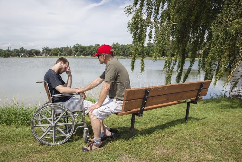Gene a consolação de seu filho adolescente em uma cadeira de rodas fotos de stock