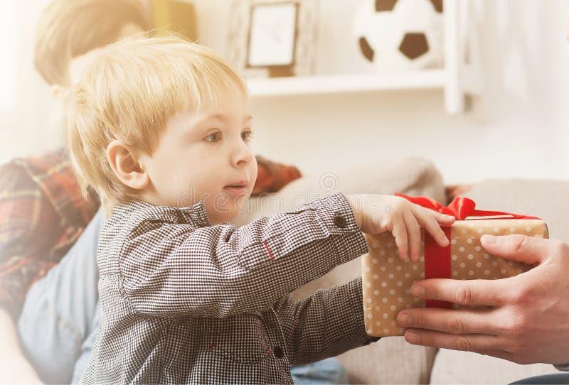 Gene a doação ao filho pequeno de um presente de Natal em casa imagem de stock