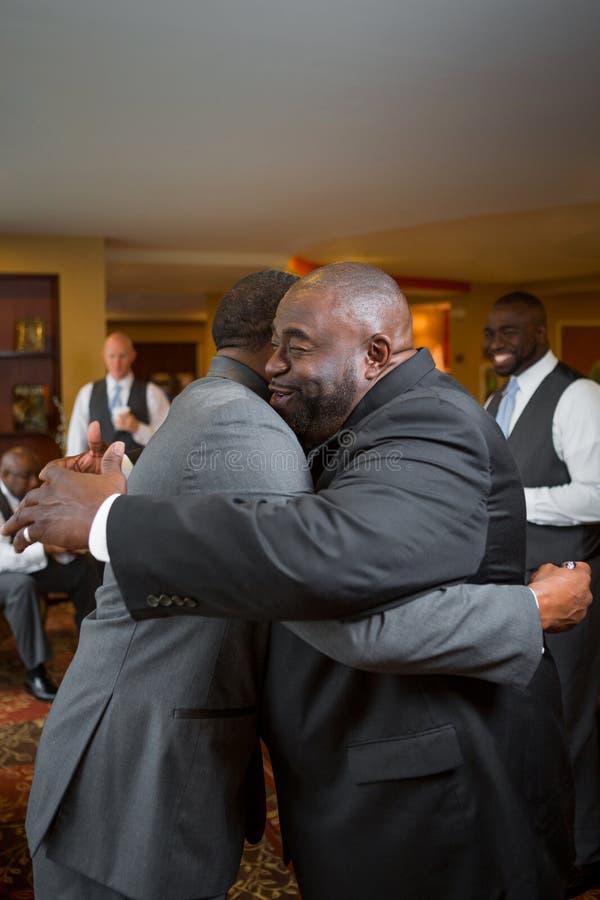 Gene e abraçando seu filho adulto em seu casamento foto de stock