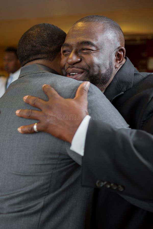 Gene e abraçando seu filho adulto em seu casamento foto de stock royalty free