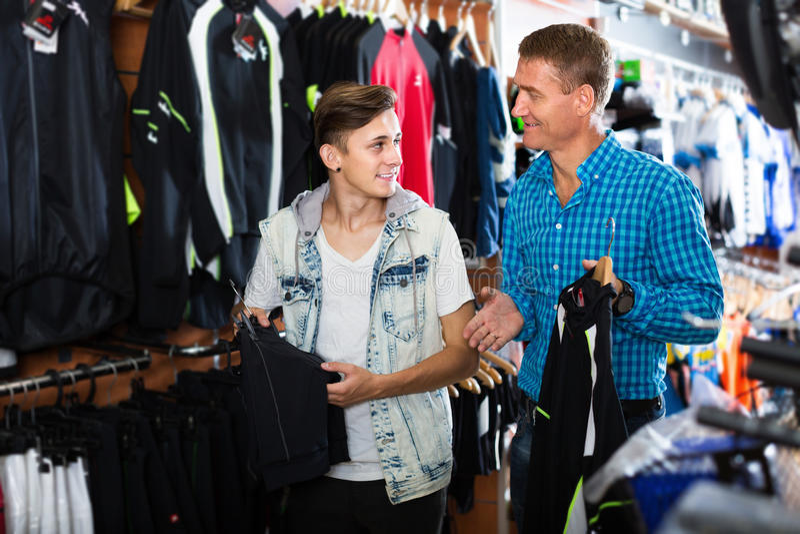 Gene e seu filho do adolescente que escolhe a roupa do esporte fotografia de stock royalty free