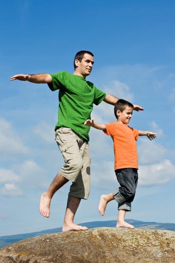 Gene e seu filho que permanece na pedra foto de stock royalty free